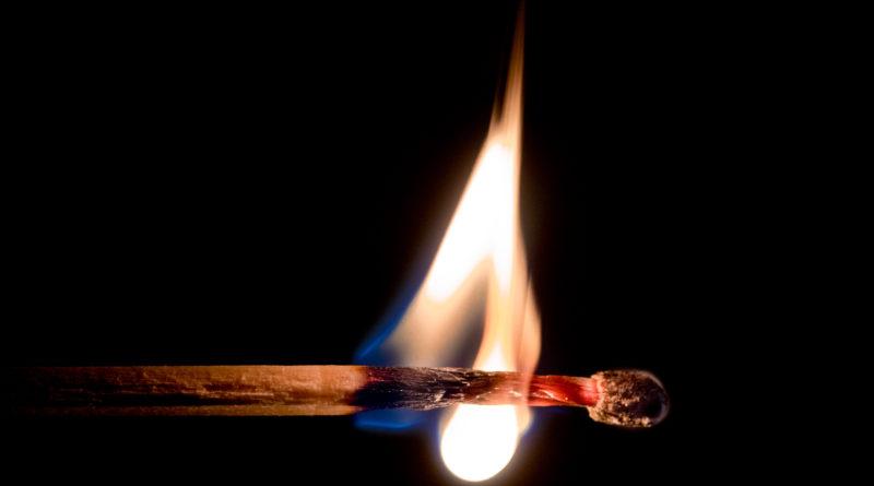 Brennendes Streichholz auf schwarzem Hintergrund